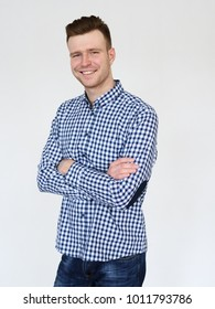 Cheerful handsome redhead young guy in black cardigan checkered shirt photographed against white wall in the studio