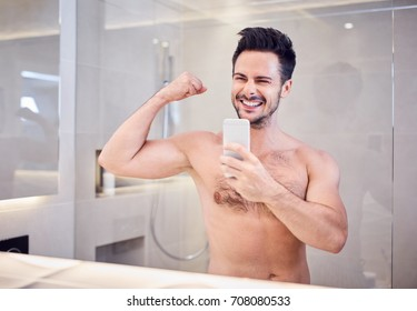 Cheerful handsome youn guy taking photo in bahtroom flexing arm