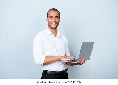 Cheerful handsome young black broker is typing on his laptop, standing in a formal wear on the pure background. So successful and intelligent, stylish and friendly