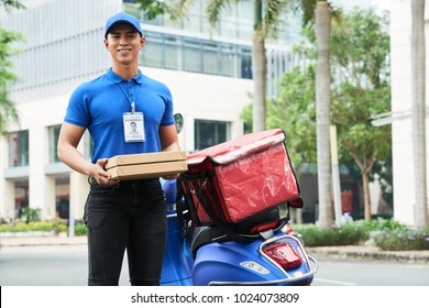 Cheerful handsome young delivery guy holding boxes with hot pizza