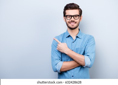 Cheerful handsome young man i glasses is showing direction and pointing with his finger