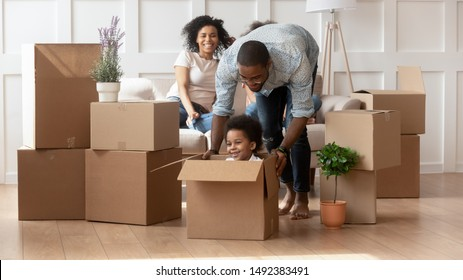 Cheerful happy african family enjoy relocation day at new modern house, father push little son sitting inside of carton box having fun riding in living room, loan mortgage, housing improvement concept