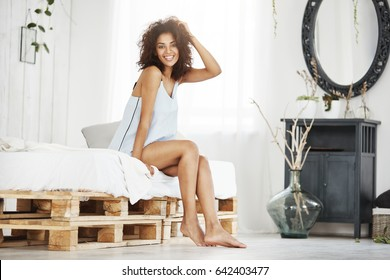 Cheerful happy african girl in sleepwear smiling looking at camera sitting on bed at home.