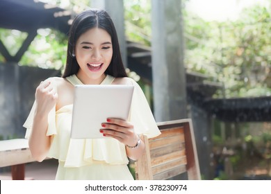 Cheerful happy Asian girl excited looking at touch pad tablet