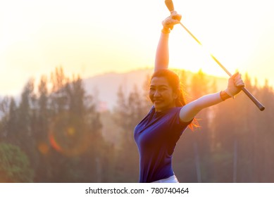 Cheerful happy asian smiling woman with a golf in the golf club in the sunny and evening sunset time, copy space.  Lifestyle Concept.
