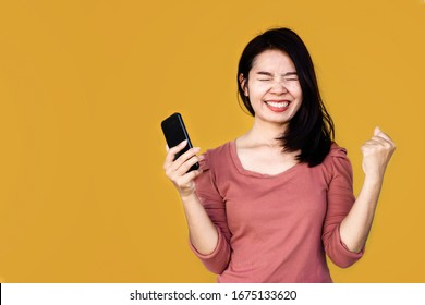 cheerful happy Asian woman get good news hand holding smart phone over yellow background