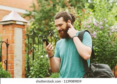 Fröhlicher, glücklicher Bärenmann, der sein Smartphone anschaut, der Musik mit Ohrhörern im Freien lauscht.