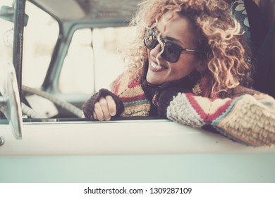 Cheerful happy beautiful caucasian young woman looking and smiling out of the window from old vintage van bus with sunglasses - travel driving concept for cute attractive girl with curly hair