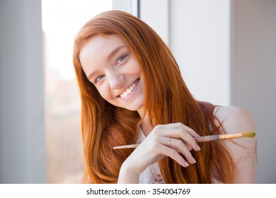 Cheerful happy beautiful redhead young woman with long hair standing near window and holding paintbrush