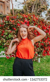 Cheerful and happy blonde woman by red bougainvillea flowers
