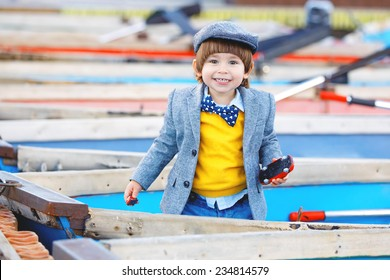Cheerful happy boy with trendy autumn or spring outfit standing in boat at harbor. Smiling toddler with fancy jacket, hat and tie bow.