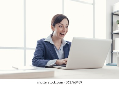Cheerful happy businesswoman sitting at office desk and receiving good news on her laptop