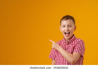cheerful, happy child points up, copying the place for the text. A smiling, enthusiastic teenage boy in a plaid shirt shows off. Advertising concept.