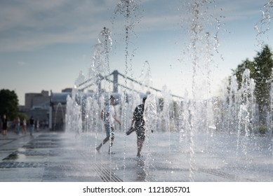Cheerful and happy children playing in a water fountain and enjoying the cool streams of water in a hot day. Hot summer.
