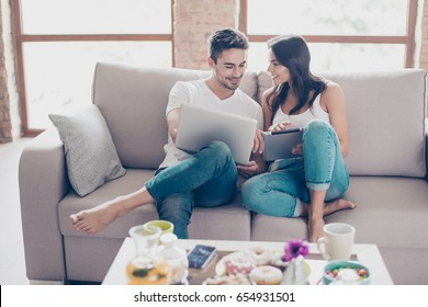 Cheerful happy couple is doing online shopping in internet at home indoors. They are on cozy beige couch in casual clothes, relaxing and buying goods easily