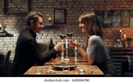 Cheerful happy couple drinking wine and having romantic dinner at home. Home date night, clinking wine glasses.