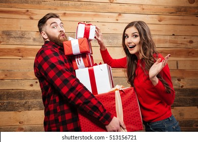 Cheerful happy couple standing with heap of xmas present boxes isolated on a wooden background