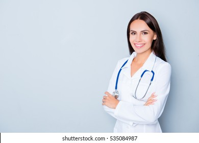 Cheerful happy doctor  with crossed hands on blue background