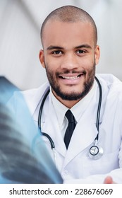 Cheerful and happy doctor with x-ray in hands. Serious doctor talking with a patient and keeps chest X-ray in hands while sitting at a table in the hospital