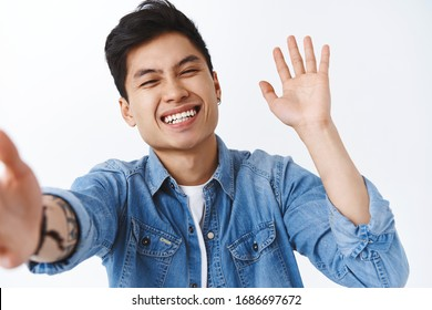 Cheerful, happy enthusiastic asian man laughing, smiling as talking to friend video-calling via mobile phone, grinning joyfully, waving hand to greet followers, saying hi or hello, white background