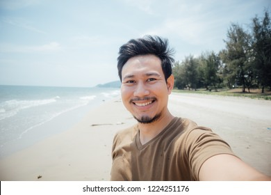 Cheerful and happy face of asian man selfie himself on the beach.