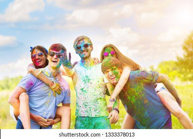Cheerful and happy friends soiled by bright colorful paints smiling and laugh on spring summer festival on nature. Company of young people having fun with holi paints. Holi party concept.