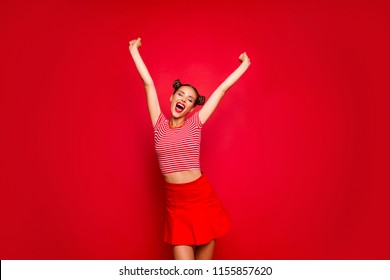 Cheerful and happy girl showing successful achieving the goal raised both hands up against red background