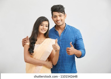 Cheerful happy Indian young couple in traditional outfit showing thumbs up .