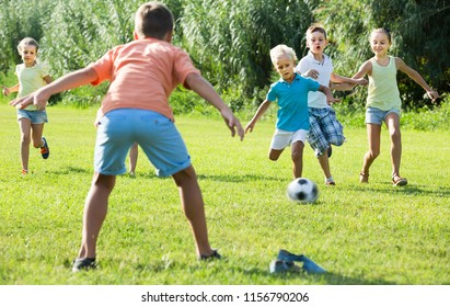 cheerful, happy kids having fun and kicking football in park on summer day