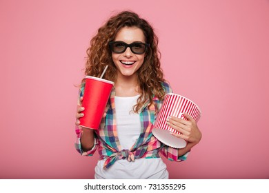 Cheerful happy lady in 3d glasses posing with cola and popcorn and smiling isolated over pink