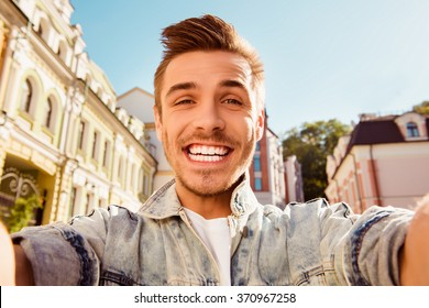 Cheerful happy man making comic selfie on the street