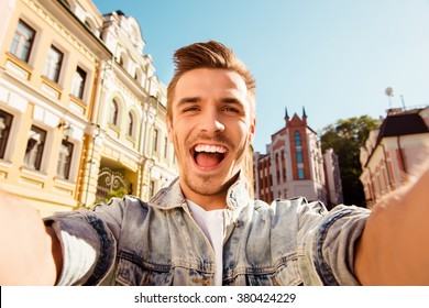 Cheerful happy man making selfie photo on the street