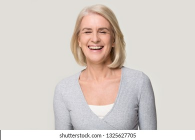 Cheerful happy mature old beautiful woman laughing at funny joke, joyful senior mid aged lady enjoying laughter with healthy dental smile having fun isolated on white grey blank studio background