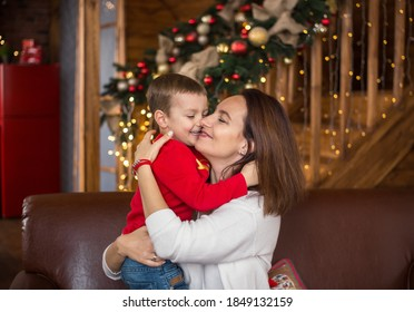 Cheerful happy mom and little son 4 years old on background of wooden house beautifully decorated before Christmas hug each other.  Cozy Christmas atmosphere - Shutterstock ID 1849132159