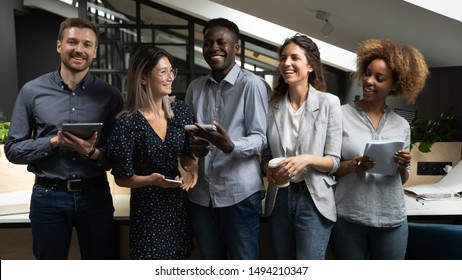Cheerful happy multicultural business team people laughing joking having fun standing together in modern office friendly positive multiracial colleagues employees good relations lifestyle communicate