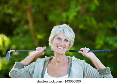 Cheerful happy older woman with a golf stick in the golf club.