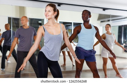 Cheerful happy   people practicing vigorous lindy hop movements in dance class