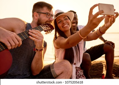 Cheerful happy pretty Latin woman in stylish hat and photographing together with African friend and crazy musician in eyeglasses biting guitar for great picture on beach.