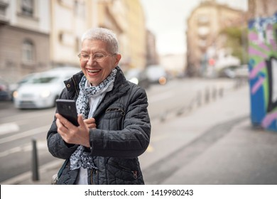 Cheerful Happy senior old woman talking on her cell phone in the street