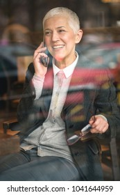 Cheerful happy senior woman having a lovely phone talk, sitting in a coffee shop