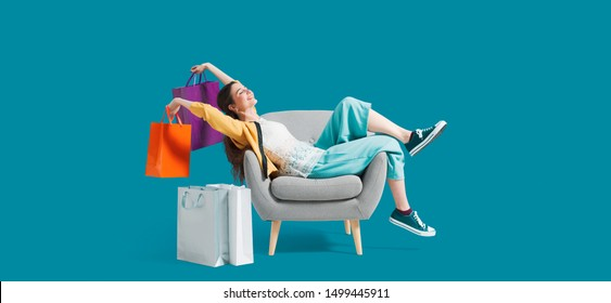 Cheerful happy shopaholic woman with lots of shopping bags, she is sitting on an armchair and celebrating with arms raised