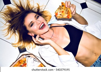 Cheerful happy smiling girl on the white floor holding and eating delicious hot pizza. Having great time. Crazy emotions. Bright make-up. Slim perfect body and junk food.