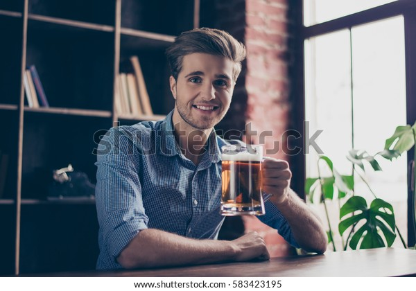 Cheerful happy smiling young man drinking beer