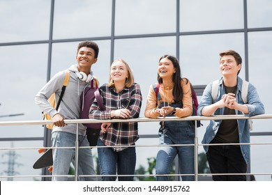 cheerful and happy teenagers smiling and looking away outside