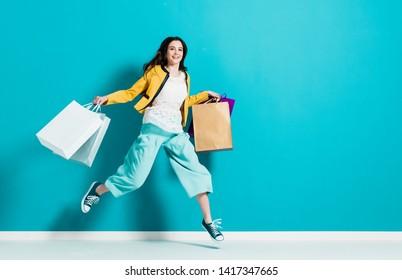 Fröhliche glückliche Frau beim Einkaufen: sie trägt Einkaufsbeutel und läuft, um die neuesten Angebote im Einkaufszentrum zu bekommen