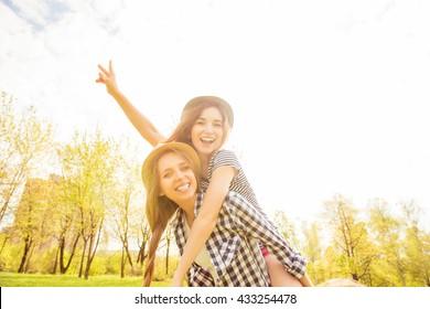 Cheerful happy woman piggybacking her pretty girlfriend