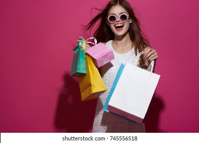 cheerful, happy woman in sunglasses with multi-colored packages on a pink background, shopping