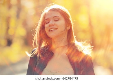 Cheerful happy young adult girl in sunlight rays and wind hair