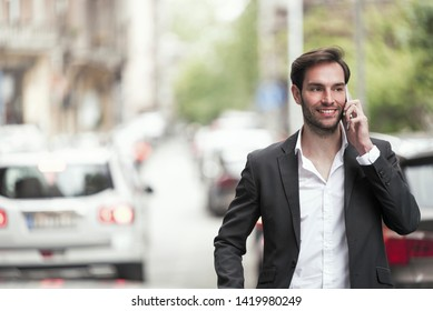 Cheerful happy young business man enjoying a nice talk over his phone, walking the streets of a city