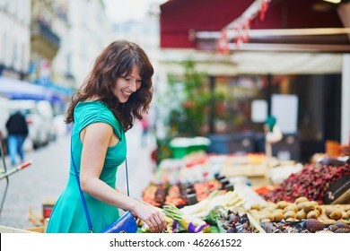 Cheerful happy young French woman selecting fruits on market in Paris, France